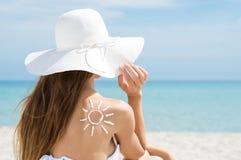 Солнце нарисованное с плечом женщины лосьона Suntan Стоковое фото RF