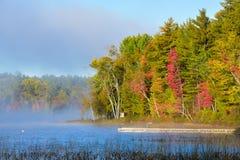 Солнце поздним летом светит на тумане утра туманном который поднимает от озера Док удлиняет в озеро от берега Стоковые Фотографии RF