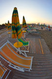 Солнце поднимает на пляж все еще дезертированное, с зонтиками и солнце Стоковая Фотография