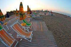 Солнце поднимает на пляж все еще дезертированное, с зонтиками Солнця a Стоковые Изображения RF