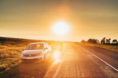 Солнце поднимая над автомобилем седана VW Volkswagen Polo Vento паркуя близко Стоковые Фотографии RF