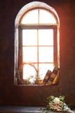 Солнце сияющее в красивом окне на котором старые книги и кладут букет цветков роз Яркий солнечный свет вечера Стоковое Изображение RF