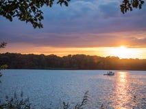 Солнце устанавливая над озером в древесинах, в летнем времени Стоковая Фотография RF