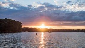 Солнце устанавливая над озером в древесинах, в летнем времени Стоковые Фото