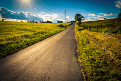 Солнце устанавливая над проселочной дорогой около перекрестных дорог, Pennsylvan Стоковые Фотографии RF