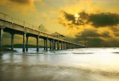 Солнце установило на море пляж с старым портом корабля внутри к глубокому морю и драматическому небу захода солнца Стоковое Изображение RF
