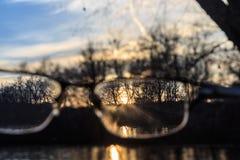 Солнце через eyegalsses во время захода солнца Стоковые Изображения