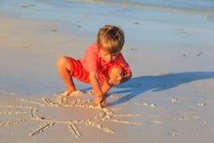 Солнце чертежа мальчика на пляже песка стоковое изображение