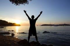 Солнце человека салютуя на море Стоковые Изображения RF