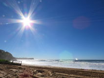 Солнце Starburst flares над пляжем Warriewood Стоковая Фотография RF
