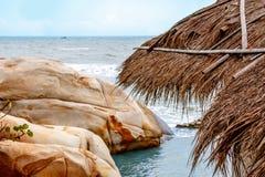 Соломенная крыша на предпосылке красочных скал и лагуны моря Стоковая Фотография