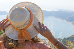 Соломенная шляпа девушки нося смотря взморье от горного вида Стоковые Фотографии RF
