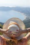 Соломенная шляпа девушки нося смотря взморье от горного вида Стоковые Фото