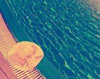 Соломенная шляпа лежит на краю бассейна, стоковые изображения rf