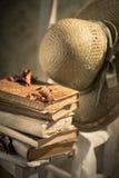 Соломенная шляпа и старые книги на стуле Стоковая Фотография RF