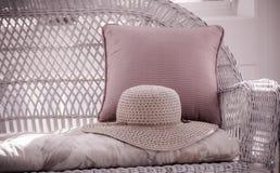 Соломенная шляпа на плетеном Loveseat Стоковая Фотография