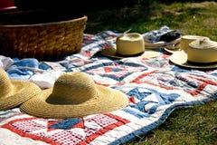 Соломенные шляпы и корзина пикника на лоскутном одеяле стоковые изображения