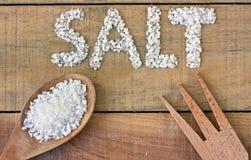 Соль в ложке на деревянном столе Стоковые Фото