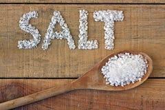 Соль в ложке на деревянном столе Стоковые Фотографии RF