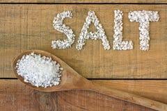Соль в ложке на деревянном столе Стоковое фото RF