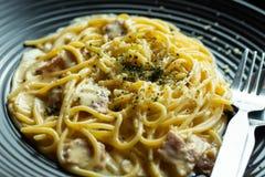 Спагетти, зажаренный сыр на черной плите на таблице Стоковые Изображения