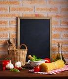 Спагетти и томаты на таблице в кухне стоковые изображения
