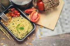 Спагетти которое подготовлено в небольшом красном лотке утюга с томатами и зернами которые выглядят аппетитными стоковое фото rf
