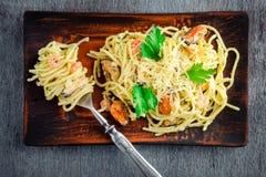 Спагетти макаронных изделий с морепродуктами в сметанообразном соусе на деревянном столе Стоковое фото RF