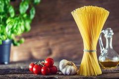 Спагетти Спагетти макаронных изделий с пармезаном и оливковым маслом сыра томатов чеснока базилика Стоковые Фотографии RF