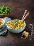 Спагетти макаронных изделий с соусом песто шпината, грецким орехом и свежими сырцовыми листьями шпината в шаре Темная предпосылка стоковая фотография