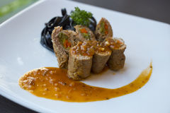Спагетти садит черную говядину на мель с оранжевым соусом Стоковые Изображения
