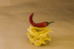 Спагетти с красной зябкой бумагой на предпосылке ремесла Стоковые Изображения