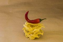 Спагетти с красной зябкой бумагой на предпосылке ремесла Стоковые Фотографии RF