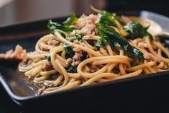 Спагетти с пошевеленным зажаренным святым базиликом стоковое изображение