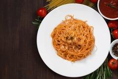 Спагетти с томатным соусом и ингридиентами на деревянном столе Стоковая Фотография