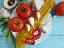 спагетти, томат, кухня перца чеснока варя овощ рецепта плиты на голубой деревянной предпосылке Стоковая Фотография RF