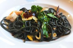 Спагетти чернил кальмара с чесноком, чилями и морепродуктами которые были помещены на белой плите Это сплавливание тайского и ита стоковая фотография rf
