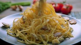 Спагетти Carbonara с ветчиной и грибами в голубой плите на деревянном столе акции видеоматериалы