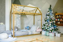 Спальня детей украшенная для рождества Большая кровать деревянной рамки с подушками и игрушками плюша, рождественской елкой с шар стоковое фото
