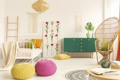 Спальня красочного и стильного ребенк boho со стулом павлина, одиночной кроватью металла и зеленым деревянным шкафом стоковая фотография
