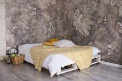 Спальня стиля просторной квартиры с рециркулированной кроватью паллета Белые и желтые постельные принадлежности на кровати с bedh стоковые фото