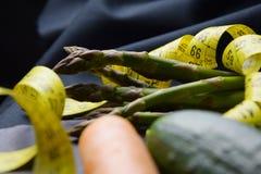 Спаржа и желтый измеряя метр на темной предпосылке стоковые изображения