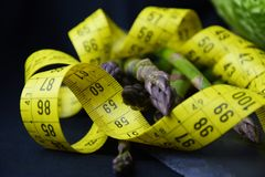 Спаржа и желтый измеряя метр на темной предпосылке стоковое изображение rf