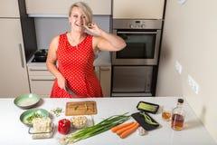 Спаржа молодой женщины сдерживая и нож держать в другой руке Стоковые Фото