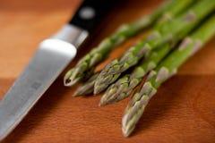 Спаржа на разделочной доске с ножом стоковые изображения rf