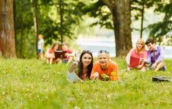 Спарите успешных студентов с учебником в парке на солнечном da Стоковое фото RF