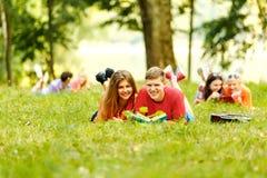 Спарите успешных студентов с учебником в парке Стоковая Фотография