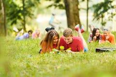 Спарите успешных студентов с учебником в парке Стоковые Фотографии RF