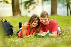 Спарите успешных студентов с учебником в парке Стоковое Изображение