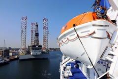 Спасательная лодка на корабле и буровая вышка в море Стоковое Фото